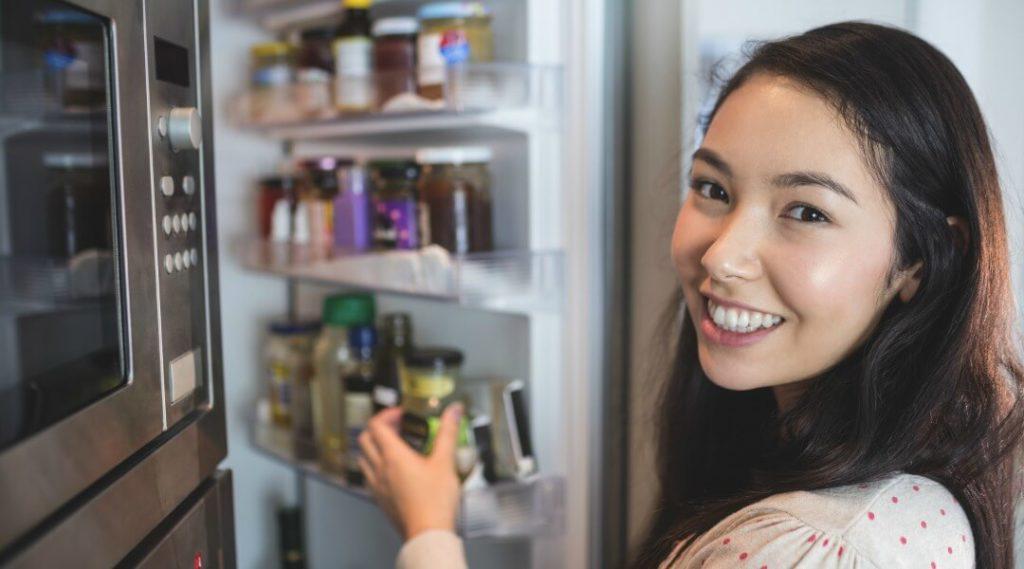 woman checking fridge storage space